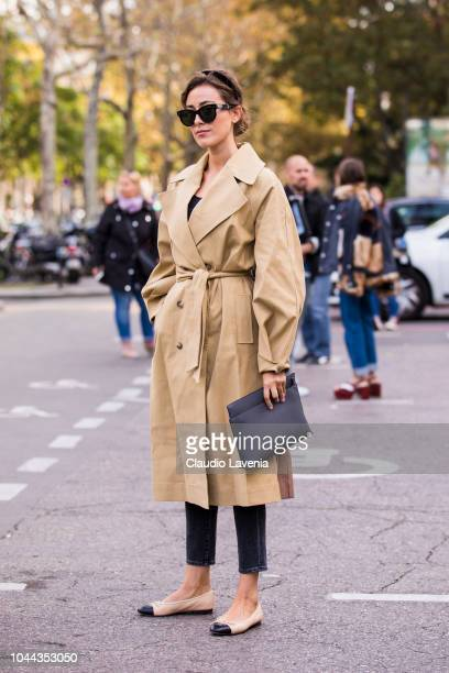 Sylvia Haghjoo wearing a long beige trench coat blue jeans Chanel shoes and black bag is seen after the Sacai show on October 1 2018 in Paris France