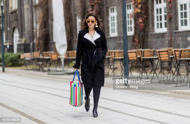 Sylvia Haghjoo wearing a striped Balenciaga bag Celine sunglasses and earrings Theory coat black Vetements pants House of Dagmar shirt black shoes on...