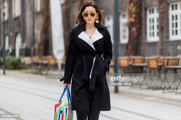 Sylvia Haghjoo wearing a striped Balenciaga bag Celine sunglasses and earrings Theory coat black Vetements pants House of Dagmar shirt black shoes on...
