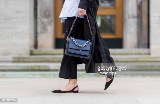 Sylvia Haghjoo wearing Eudon Choi black pants and white blouse a black Bassike coat navy Marni bag blue JW Anderson earings Paul Andrew flat shoes on...