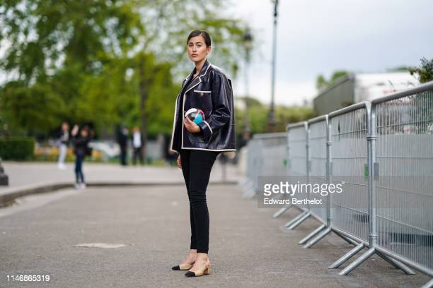 Sylvia Haghjoo wears a black Chanel leather jacket with white lines, a Chanel bag in the form of a multicolor plastic sphere, Chanel slingback shoes,...