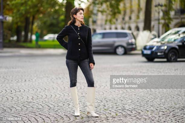 Sylvia Haghjoo wears a black tweed jacket with golden buttons, gray denim jeans, white pointy high boots, a bag, outside Chanel, during Paris Fashion...