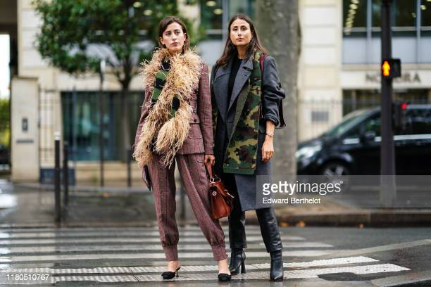 Sylvia Haghjoo wears a brown and burgundy Prince of Wales check jacket, assorted baggy pants, a black and green knit scarf decorated with feathers, a...