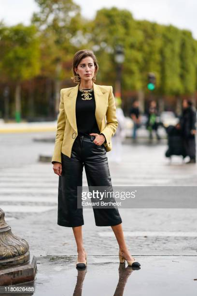 Sylvia Haghjoo wears Chanel earrings, a Chanel necklace, a yellow jacket, a black top, black leather wide-legs crop pants, Chanel slingback pumps,...