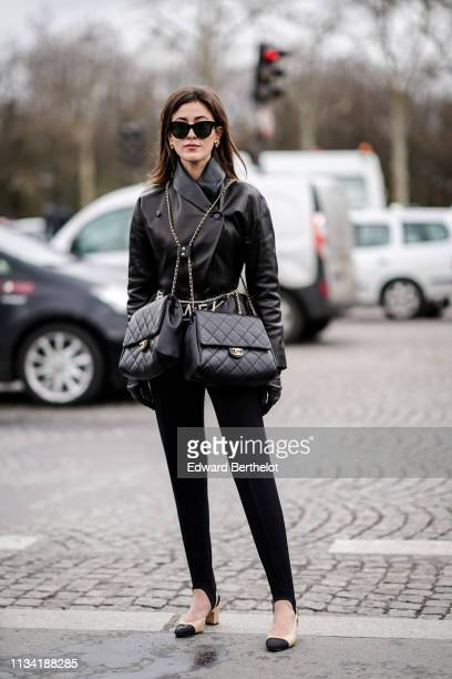 Sylvia Haghjoo wears sunglasses a black leather jacket double Chanel bags black pants Chanel slingback shoes outside Chanel during Paris Fashion Week...