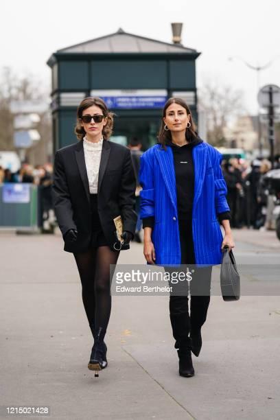 Sylvia Haghjoo wears sunglasses, a black oversized blazer jacket, a white top, a black skirt ; Julia Haghjoo wears earrings, a black Holzweiler...
