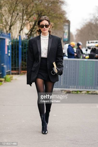 Sylvia Haghjoo wears sunglasses, a black oversized blazer jacket, a white top, a black skirt, black leather gloves, outside Balmain, during Paris...