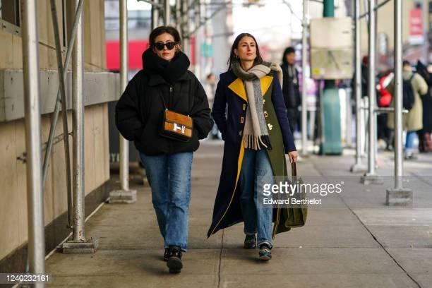 Sylvia Haghjoo wears sunglasses, a large scarf, a black oversized puffer jacket, a brown Hermes bag, blue jeans ; Julia Haghjoo wears a wool fringed...