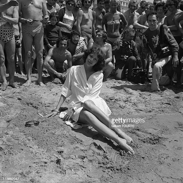 Sylvia Kristel poses on a beach with fans and photographers behind her in Cannes during the Cannes Film Festival in 1970's in Cannes, France.