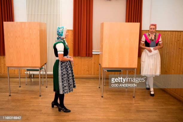 Sylvia Panoscha and her daughter Juliane wearing traditional Sorbian dresses leave a voting booth prior to cast their ballots for state elections in...