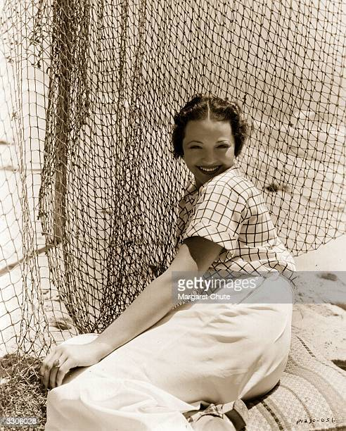 Sylvia Sidney , dark haired leading lady of the 1930's, on the beach in front of her Malibu home.