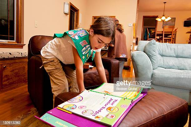 Sylvia Wolk a Girl Scout looks through a Girl Scouts binder that includes descriptions of badges at home in Bedford Mass on Thursday Nov 3 2011 The...