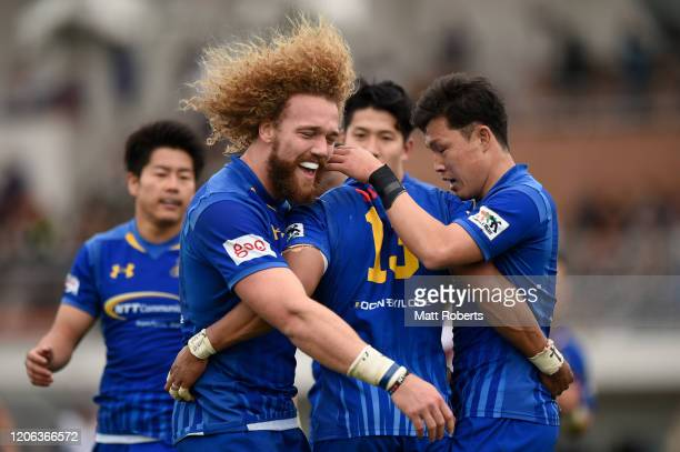 Sylvian Mahuza of NTT Communications ShiningArcs celebrates scoring a try with Willem Britz and Yuki Ikeda during the Rugby Top League match between...