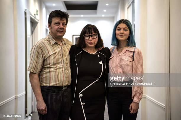 Sylvie and Dominique Mennesson and their daughter Fiorella pose at their lawyer Patrice Spinosi 's office following a press conference in Paris on...
