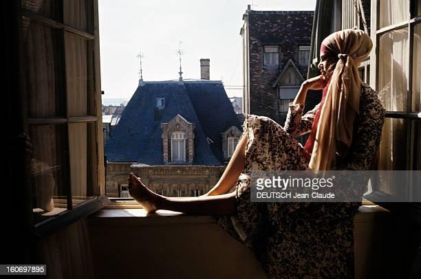 Sylvie Fennec For The Summer Fashion 'midi Midnight' In Deauville Sylvie FENNEC en robe à fleurs un long foulard noué dans ses cheveux est assise sur...