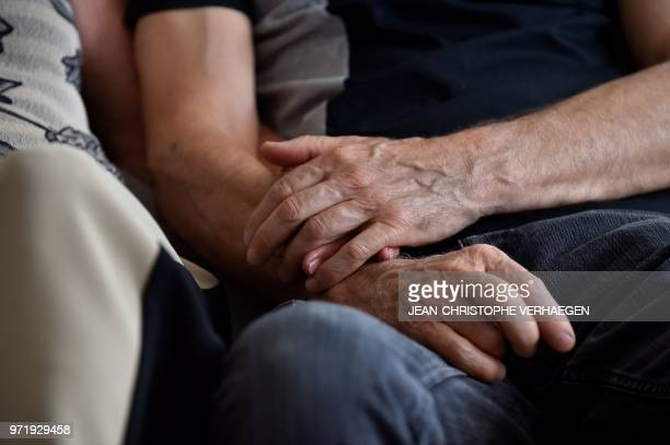 Sylvie Richard who suffers from an incurable form of cancer holds hands with her partner Bernard Lacour during an interview on June 1, 2018 in...