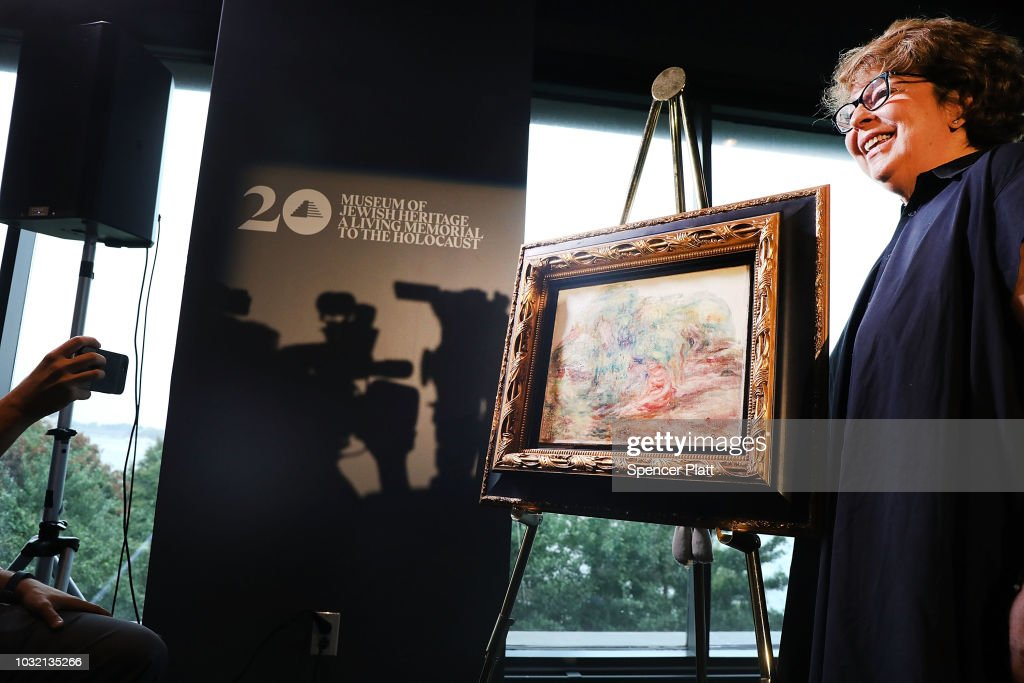 Sylvie Sulitzer poses with the recovered Impressionist painting 'Two Women in a Garden,' painted in 1919 by Pierre-Auguste Renoir on September 12, 2018 in New York City. The artwork, which originally belonged to Sulitzer's grandfather Alfred Weinberger, was confiscated by the Nazis in Paris during the World War II. The only living heir, Sylvie Sulitzer became aware of the work in 2013 when the painting was listed for sale at Christie's in New York. With the help of the FBI and the U.S. Attorney's office in Manhattan, the painting was finally returned to her at a ceremony at the Museum of Jewish Heritage in Lower Manhattan.