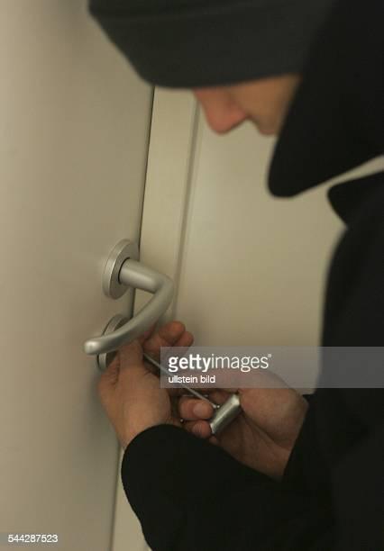 Symbol Einbruch Einbrecher mit Dietrich an einer Wohnungstür