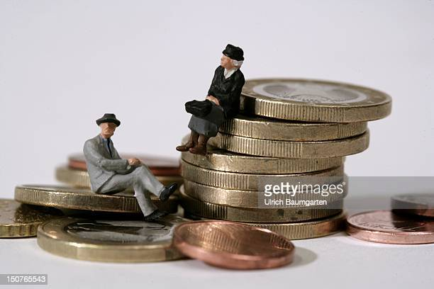 GERMANY BONN Symbol image oldage pension long term care insurance Ops Two figurines old woman and old man sit on coins