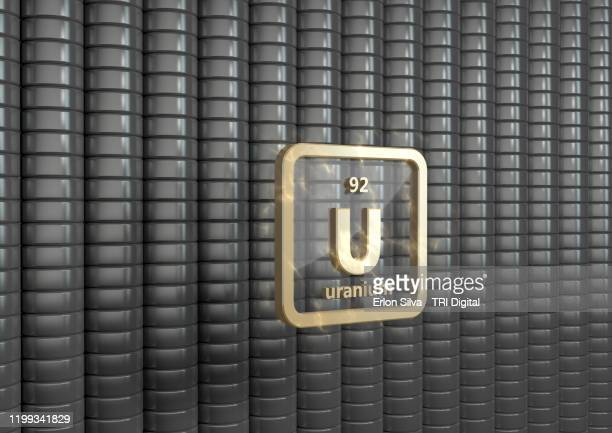symbol of uranium in front of a stack of enriched uranium - uranium stock pictures, royalty-free photos & images