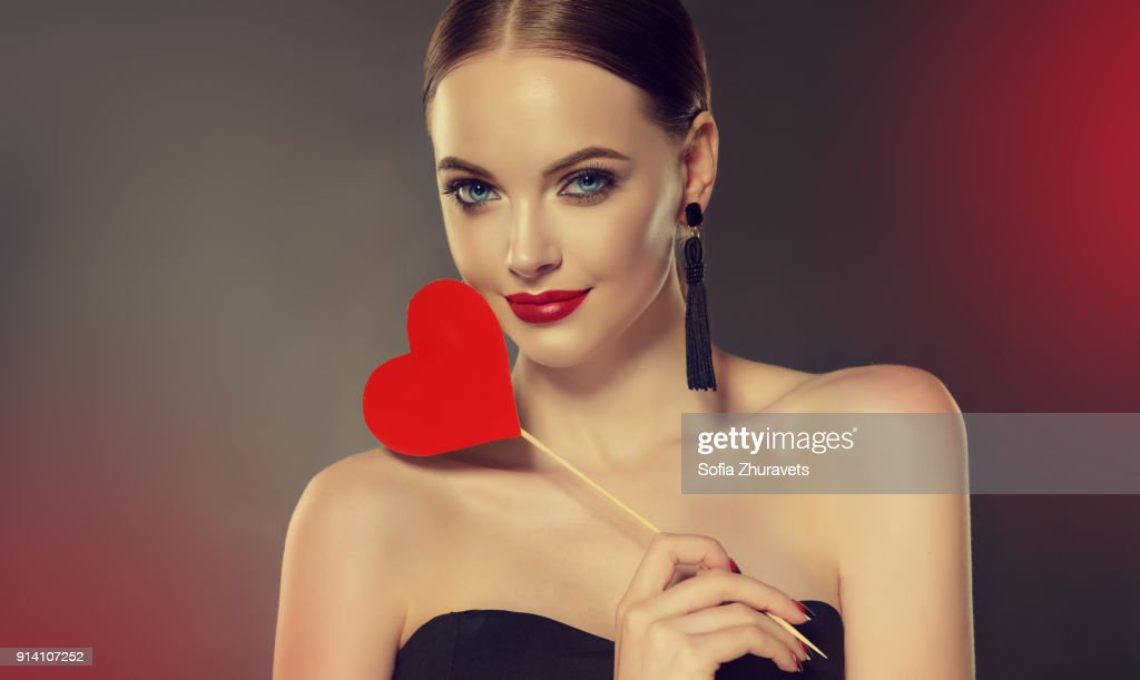 Symbol of Valentine's day on the hand of beautiful woman. : Stock Photo