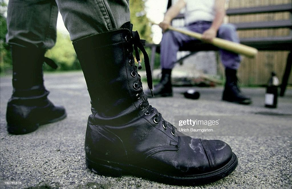 Symbol of violence,,,men's legs with army boots, bottles of beer, baseball bat. : News Photo