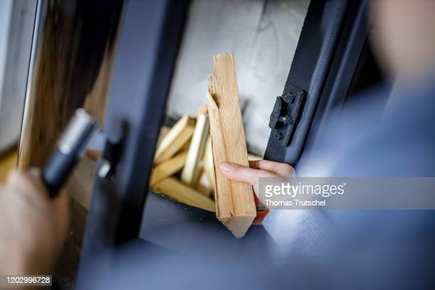 Symbol photo A woman is stacking firewood in a fireplace on February 21 2020 in Berlin Germany