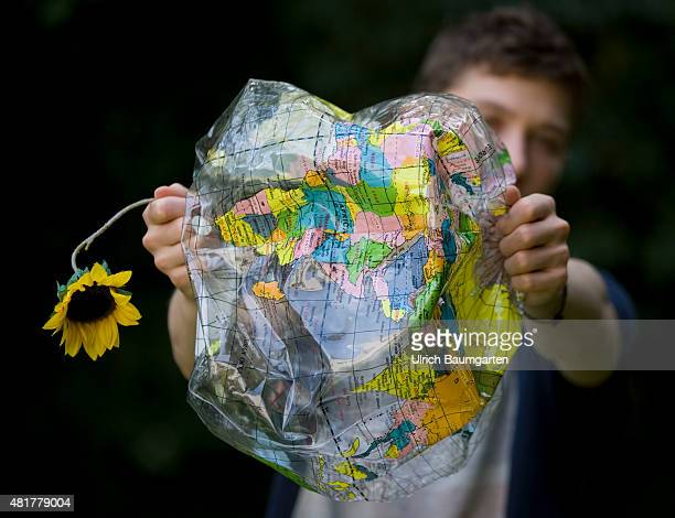 Symbol photo about climate global warming enviroment and enviromental protection etc Our picture shows a young person with a crumbled globe and a...