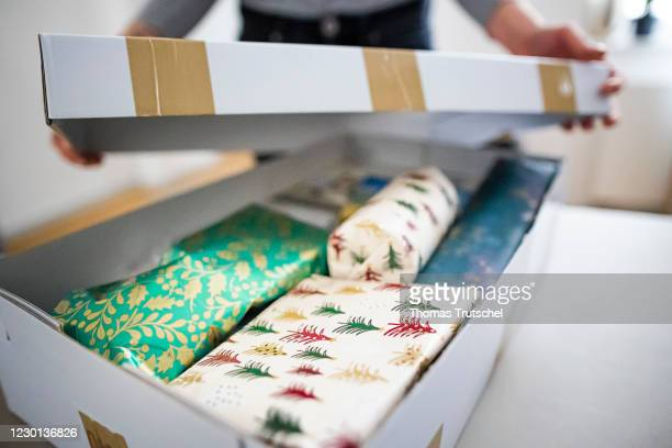 Symbol photo about sending Christmas gifts by mail. A woman opens a package with Christmas gifts on December 15, 2020 in Berlin, Germany.