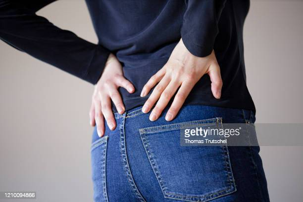 Symbol photo back pain A woman touches her aching back with her hands on April 13 2020 in Berlin Germany