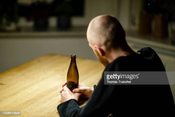 Symbol photo on the subject of alcoholism A man sitting alone at home at a table holding a bottle of beer in his hand on March 25 2020 in Berlin...