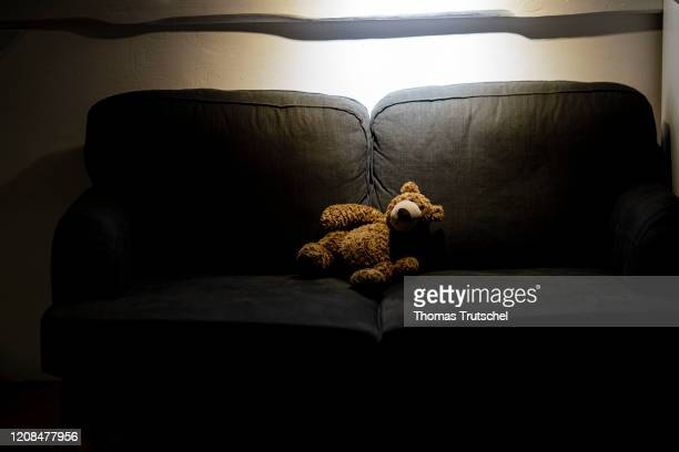 Symbol photo on the subject of child abuse a teddy is sitting alone on a couch in the dark on March 25 2020 in Berlin Germany