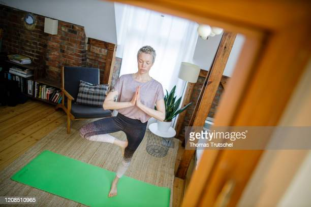 Symbol photo on the subject of fitness A woman is exercising yoga at home in her living room on March 26 2020 in Berlin Germany