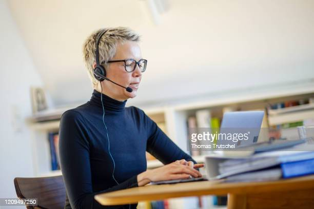 Symbol photo on the subject of home office A woman is sitting at her desk at home She wears a headset and takes part in a video conference on April...