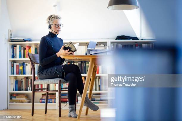 Symbol photo on the subject of home office. A woman is sitting at her desk at home. She wears a headset and takes part in a video conference on April...