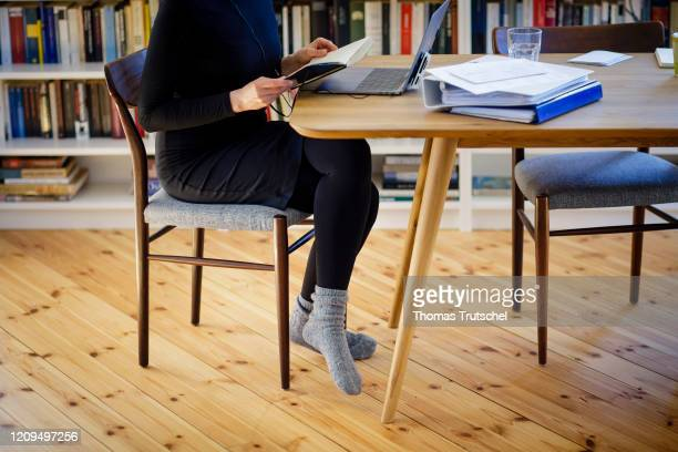 Symbol photo on the subject of home office. A woman is sitting at her desk at home and works on a laptop on April 06, 2020 in Berlin, Germany. During...