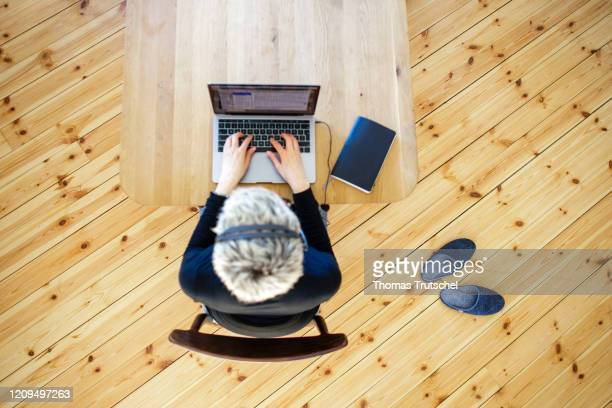Symbol photo on the subject of home office. A woman is sitting at her desk at home. She wears a headset on April 06, 2020 in Berlin, Germany. During...