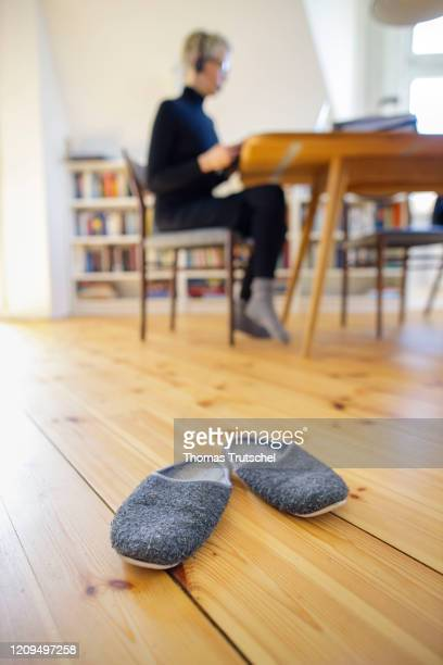 Symbol photo on the subject of home office A woman sits at her desk at home and works on something Slippers are placed in the foreground on April 06...