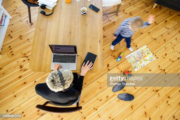Symbol photo on the subject of home office. A woman sits at her desk at home and works. A child is playing next to her on April 06, 2020 in Berlin,...
