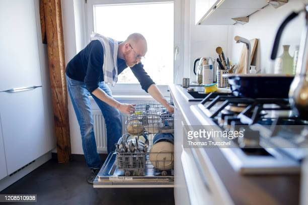 Symbol photo on the subject of housework A man puts away a dishwasher on March 26 2020 in Berlin Germany