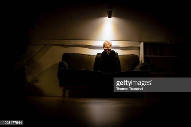 Symbol photo on the subject of loneliness and isolation A woman sits alone on the couch at night and covers her face with her hands on March 25 2020...