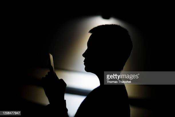 Symbol photo on the subject of loneliness and isolation A woman sits on the couch at night and looks into a smartphone on March 25 2020 in Berlin...
