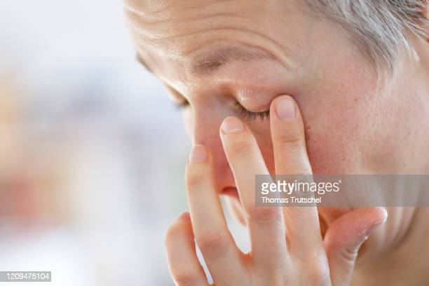 Symbol photo on the subject of the risk of infection A woman grabs her face with her hand and rubs her eye on April 05 2020 in Berlin Germany In...