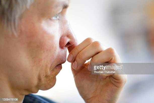 Symbol photo on the subject of the risk of infection A woman grabs her face with her hand and rubs her nose on April 05 2020 in Berlin Germany In...