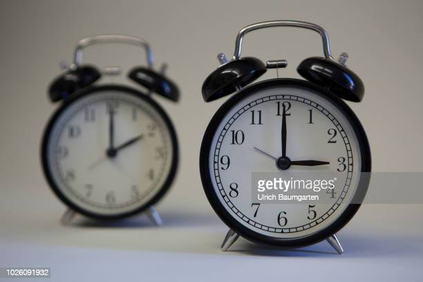 Symbol photo on the subject summer and winter time Alarm clocks with the clock pointers to 3 o'clock and 2 o'clock