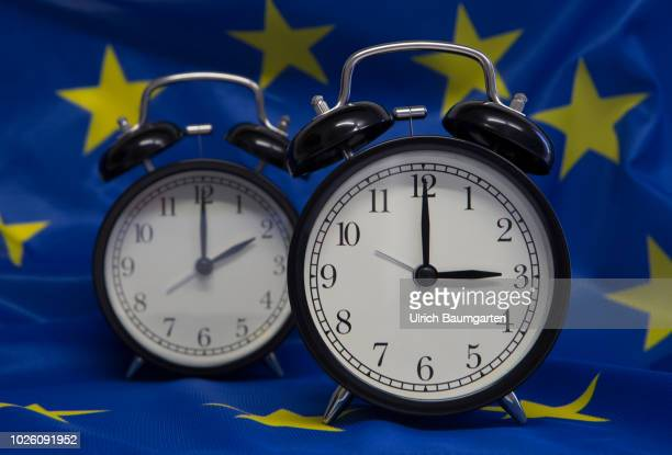 Symbol photo on the subject summer and winter time Alarm clocks with the time 3 o'clock and 2 o'clock on a uropean flag