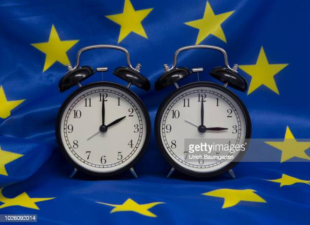Symbol photo on the subject summer and winter time. Alarm clocks with the time 3 o'clock and 2 o'clock on a uropean flag.
