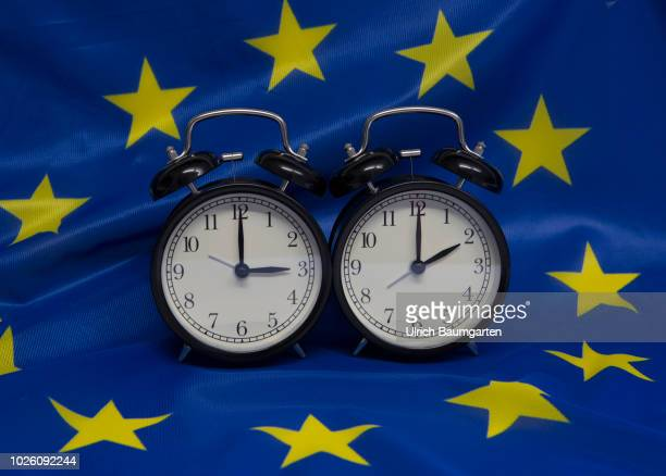 Symbol photo on the subject summer and winter time Alarm clocks with the clock pointers to 2 o'clock and 3 o'clock on a European flag