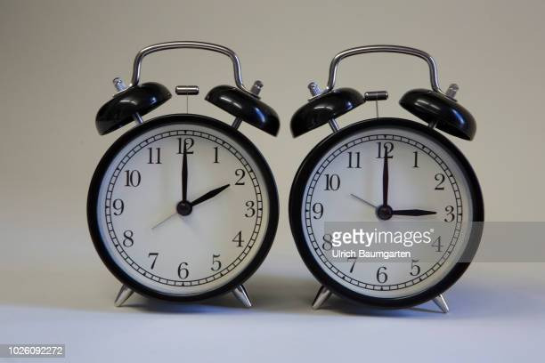 Symbol photo on the subject summer and winter time. Alarm clocks with the clock pointers to 3 o'clock and 2 o'clock.
