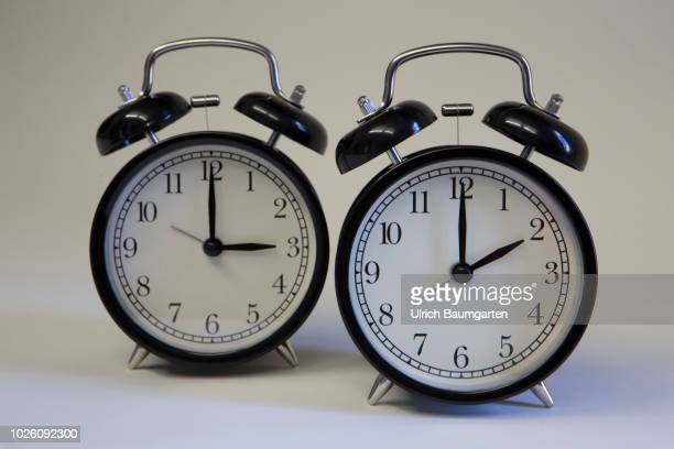 Symbol photo on the subject summer and winter time Alarm clocks with the clock pointers to 2 o'clock and 3 o'clock